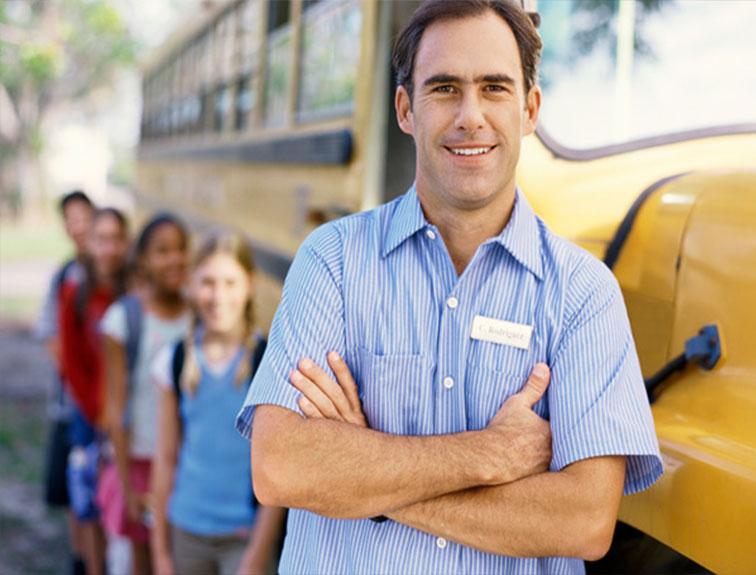 picture of School Bus Driver in Uniform leaning against the bus with school children standing behind him