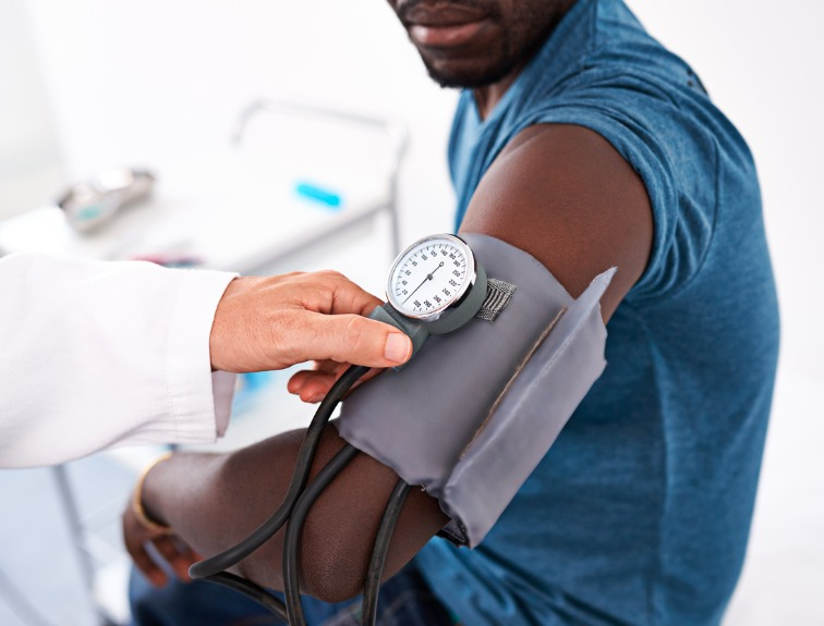 photo image of a male patient sitting with a blood pressure cuff on his arm, while a doctor takes a reading