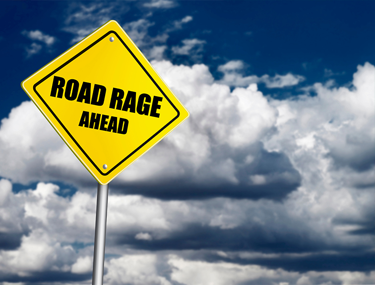 """yellow street sign that reads """"road rage"""" in bold black letters against a background of fluffy clouds in a dark blue sky"""