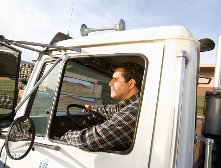 man driving truck looking in side mirror