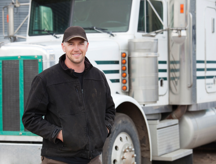 man with hands in pocket smiling in front of white semi truck