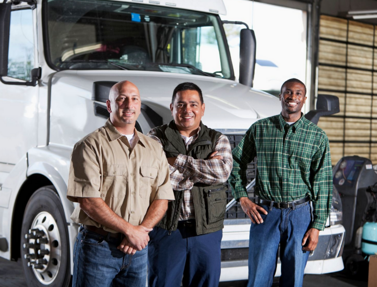 three men smiling in front of semi truck parked in garage