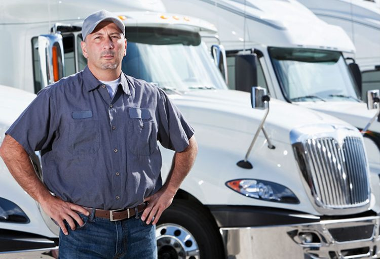 truckdriver with hands on hips in front of semi trucks
