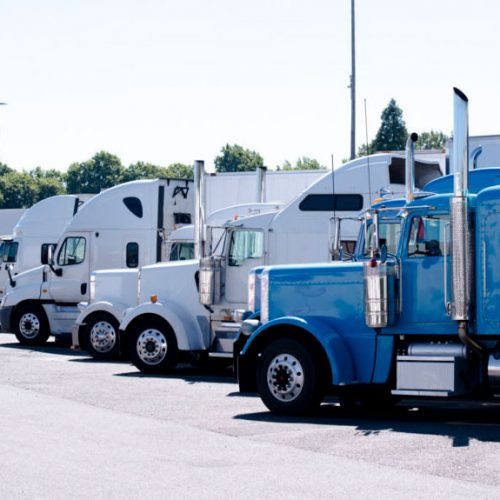 An image of 5 different semi trucks parked in a row at a truck stop.