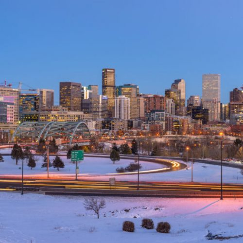 An image of the Denver skyline on a cold winter evening, the streets and highway (US Interstate 25) are filled with heavy rush-hour traffic.