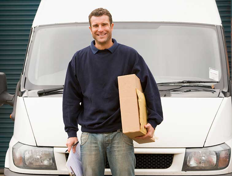 image of young male standing in front of a nondescript white delivery truck holding a box and paperwork