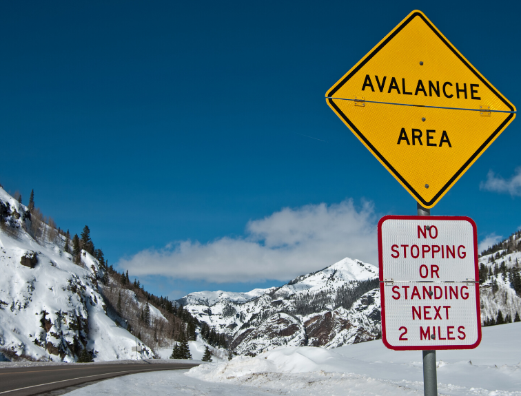 "Image of road through snow covered mountains and road sign that reads ""avalanche area""."