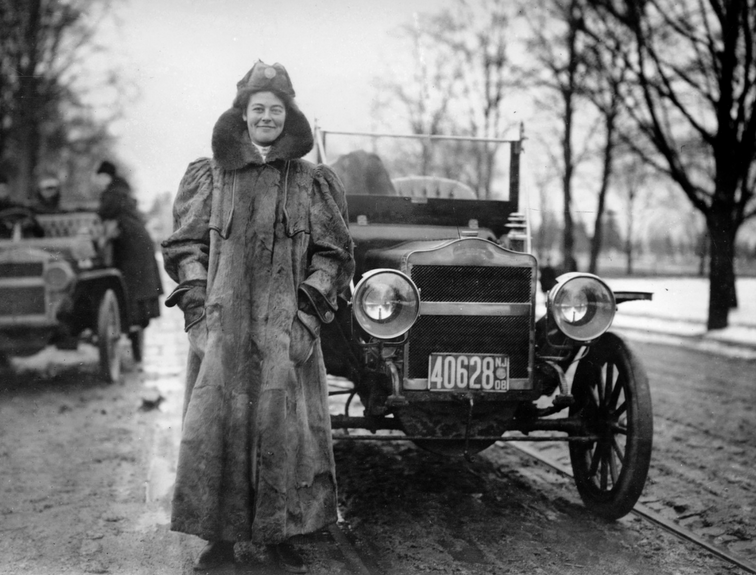 black and white photo of lady standing in front of antique car