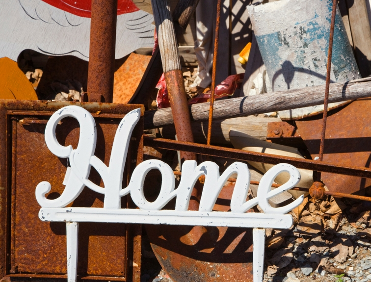 metal home sign in front of rusted tools