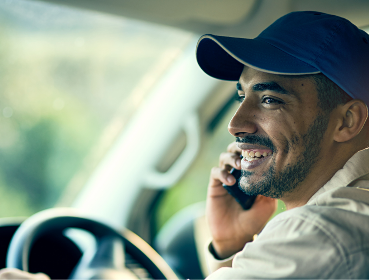 truck driver smiling while talking on the phone in cab of truck