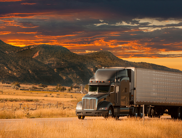 semi driving with mountains and sunset in the background