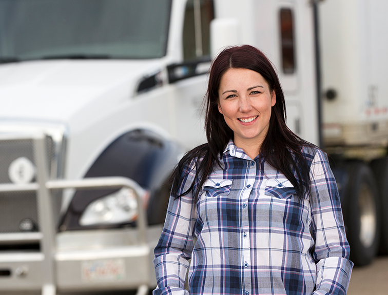 Image of women trucker standing in front of CDL truck