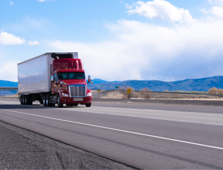 Image of red CDL truck driving on highway with mountains and blue skies in the background